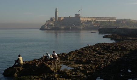 Cubans fishing on the rocks facing Morro Castle in Havana.