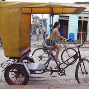 Woman bicycling by an empty pedicab on a street in Baracoa, Cuba