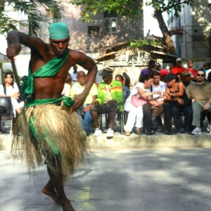 Afro-Cuban man dancing in grass skirt on street with audience in background