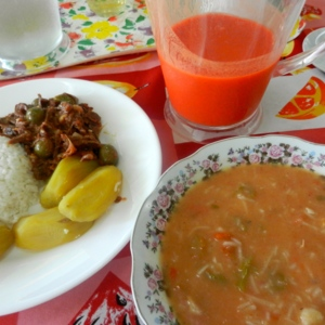 Closeup of meal sitting on table including bowl of soup and drink