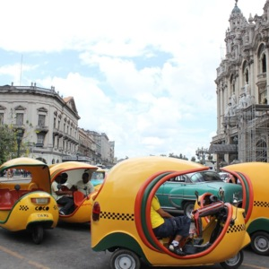 A group of Cocotaxi drivers waits for customers in downtown Havana