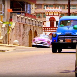 Colorful antique cars parking along the sides of a busy Havana street