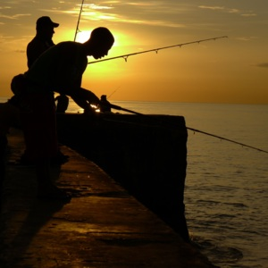 Cubans fishing along Malecón in Havana at sunset