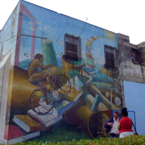 A wall mural depicts a bicyclist climbing a stairway of books to the sun.  Cuba has one of the highest literacy rates in the world.
